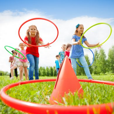 Two group of kids playing with colorful hoops and throw them on cones while competing with each other during summer sunny day