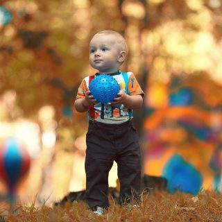 autumn child playing ball in the park