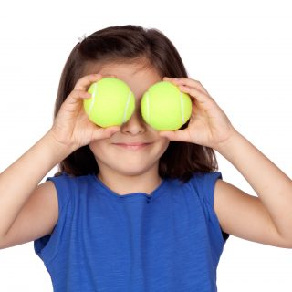 Brunette little girl with two tennis balls isolated on a over white background